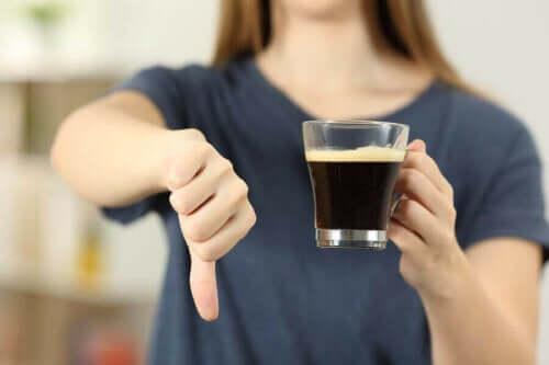 Samband mellan kaffe och hjärtattack: en kvinna ger tummen ner för kaffe.