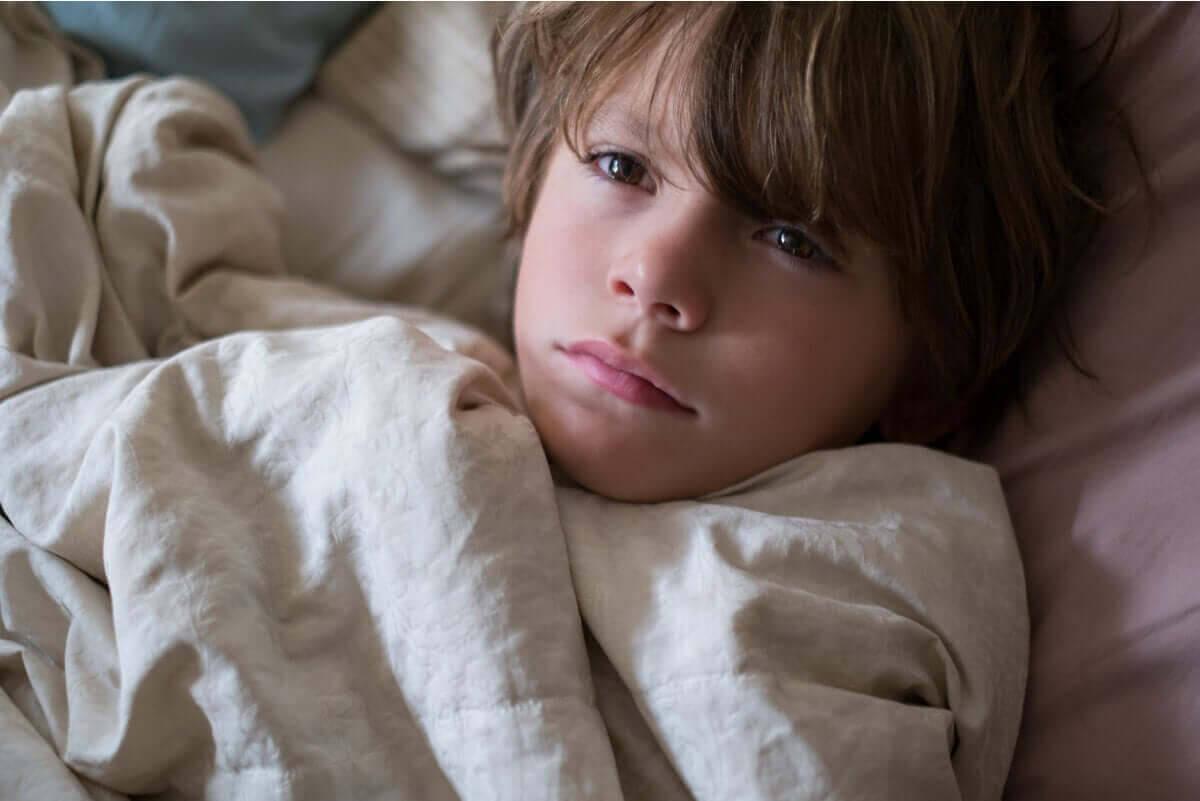 mörka ringar under ögonen: pojke i säng som inte sover