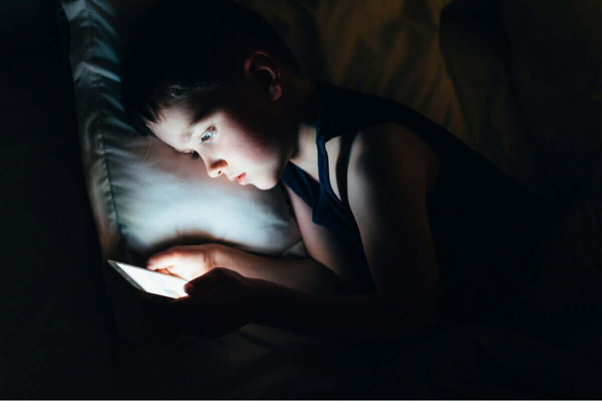 mörka ringar under ögonen: barn med skärm i säng