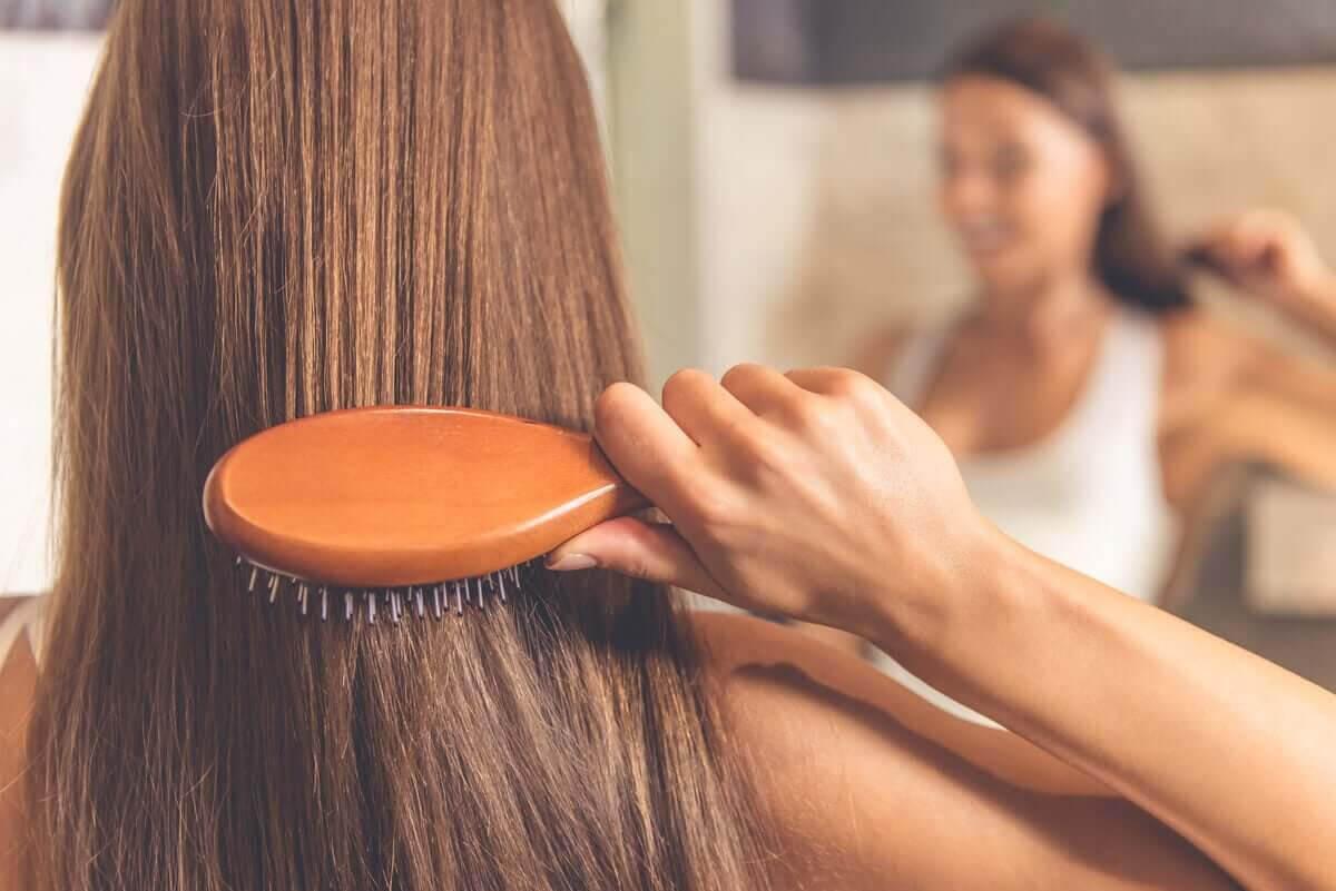rengör din hårborste: kvinna borstar håret