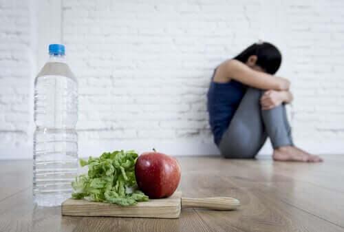 Överdriven oro för din hälsa: ihopkrupen kvinna med vattenflaska, salladsblad och äpple