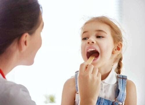 Mononukleos hos barn: läkare tittar i munnen på barn
