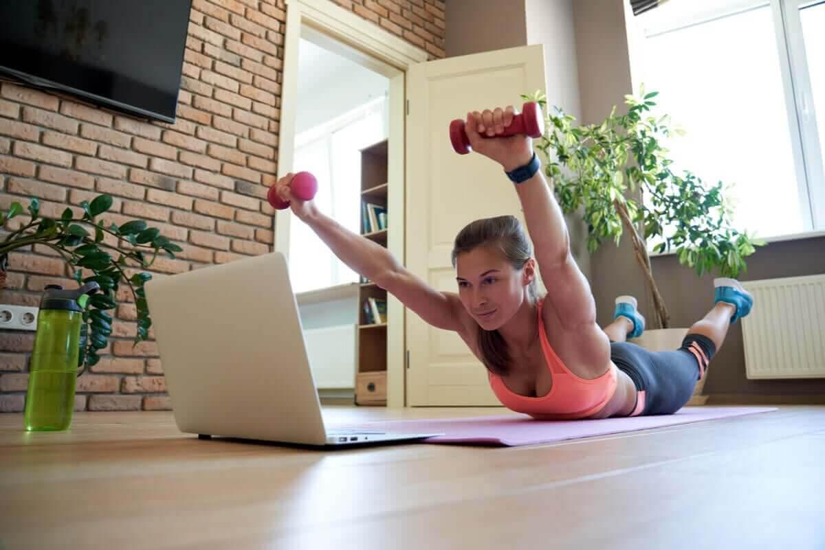 ryggövningar med hantlar: kvinna gör Stålmannen framför laptop