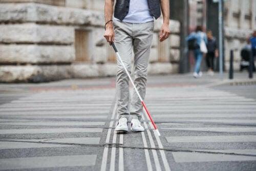 Synkador och synnedsättningar: person går över gatan med hjälp av vit käpp