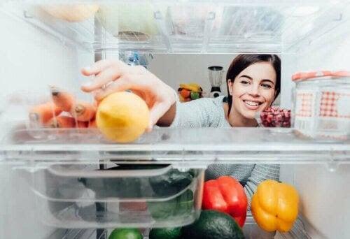 Korskontaminering från skadliga virus och bakterier: kvinna sträcker sig efter en citron i ett kylskåp