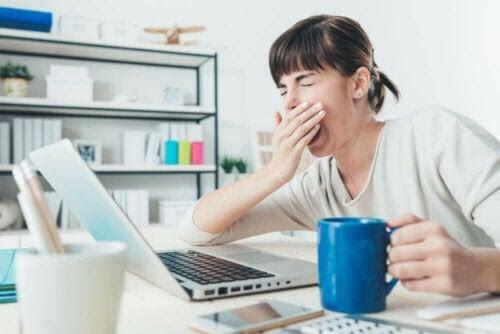 morgontrött och sömndrucken kvinna vid laptop