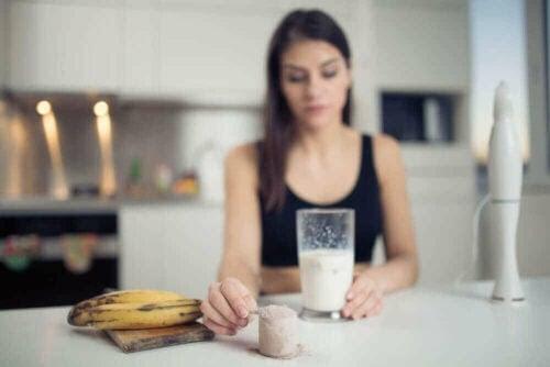 fördelar med bananer för idrottare: kvinna med bananer gör en shake