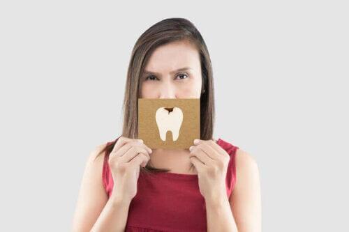 kvinna håller upp bild av kariesangripen tand
