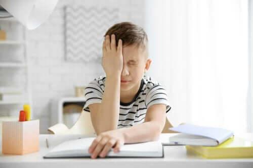 Barn med huvudvärk försöker göra hemläxa.
