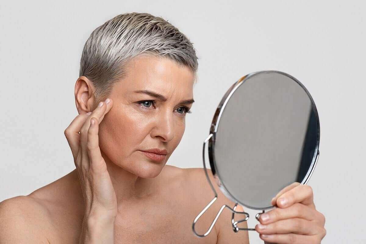 Kvinna tittar på sina rynkor i en spegel.