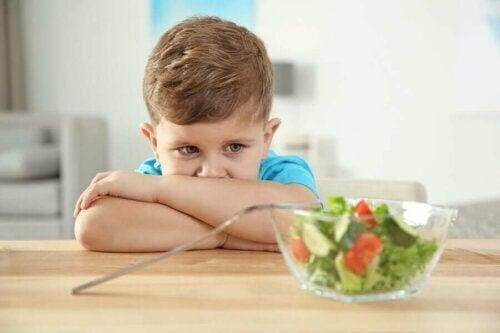 pojke tittar skeptiskt på sallad
