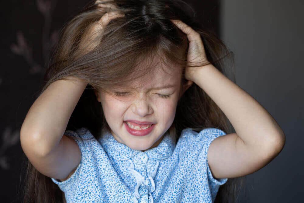 Håravfall hos barn: flicka drar sig i håret