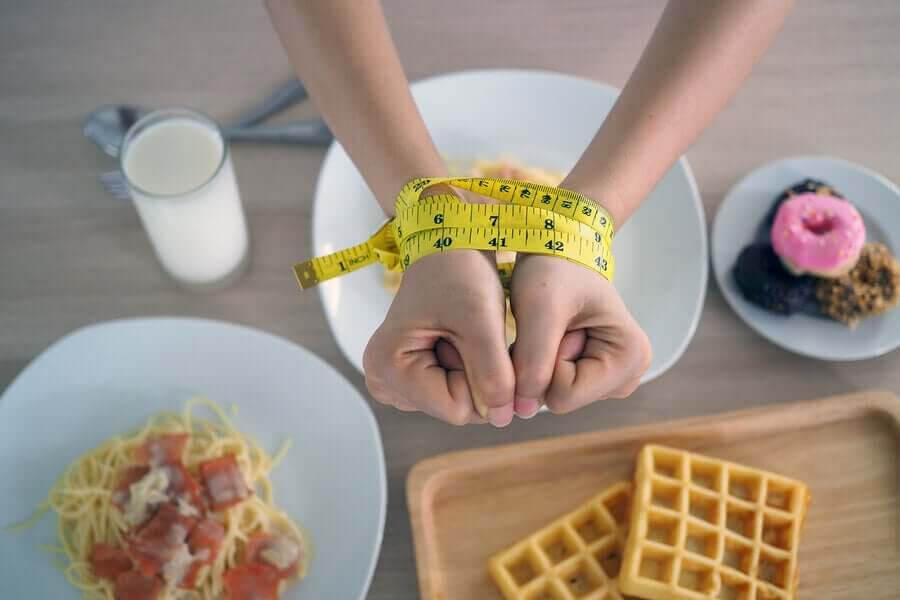 händer ihopbundna med måttband över kolhydratrik mat