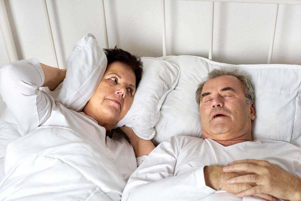 Hypotrofi i näsmusslorna: kvinna håller för öronen bredvid snarkande man