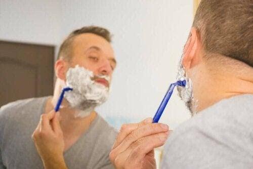 fel vid rakning: man vid spegel rakar sig