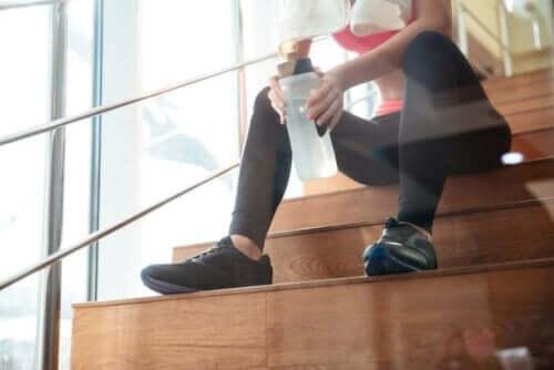 Kvinna dricker vatten när hon tränar.