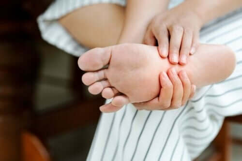 Person masserar sin onda fot.
