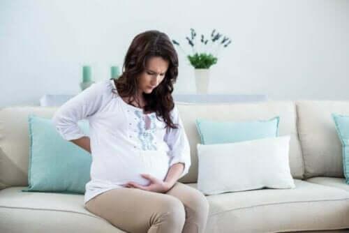 Menstruationskramper under graviditeten: gravid kvinna på soffa