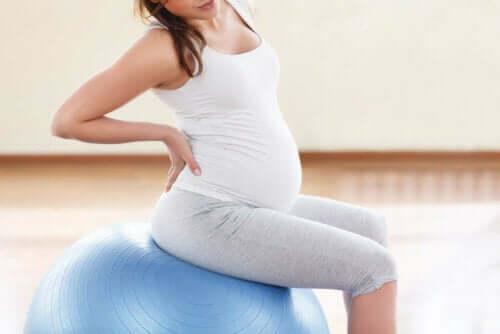 Menstruationskramper under graviditeten: gravid kvinna på yogaboll