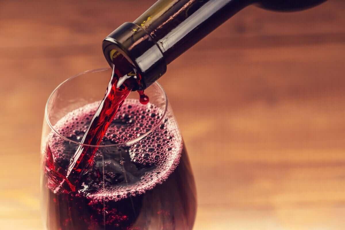 häller upp rött vin i glas