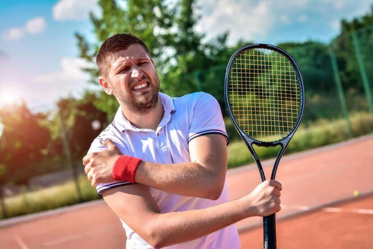 man med tennisracket har ont i axeln