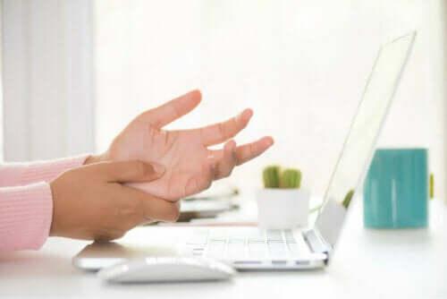 person med Domningar i händerna vid dator