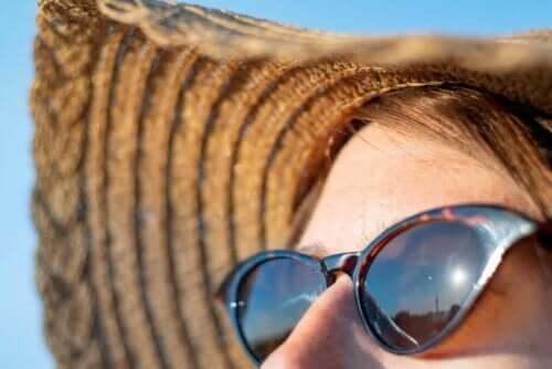 Hälsoeffekterna av solens strålar: kvinna i solhatt och solglasögon