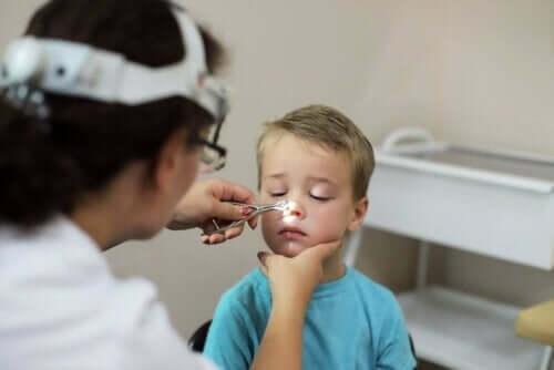 läkare undersöker barn för Förstorade adenoider
