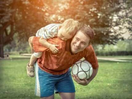 En pojke rider på sin pappas rygg.