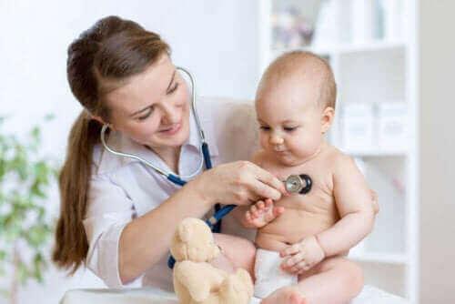 läkare undersöker baby efter Gropar vid korsbenet