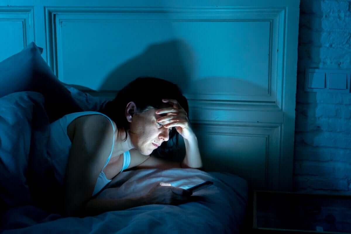person tittar på mobil i sängen