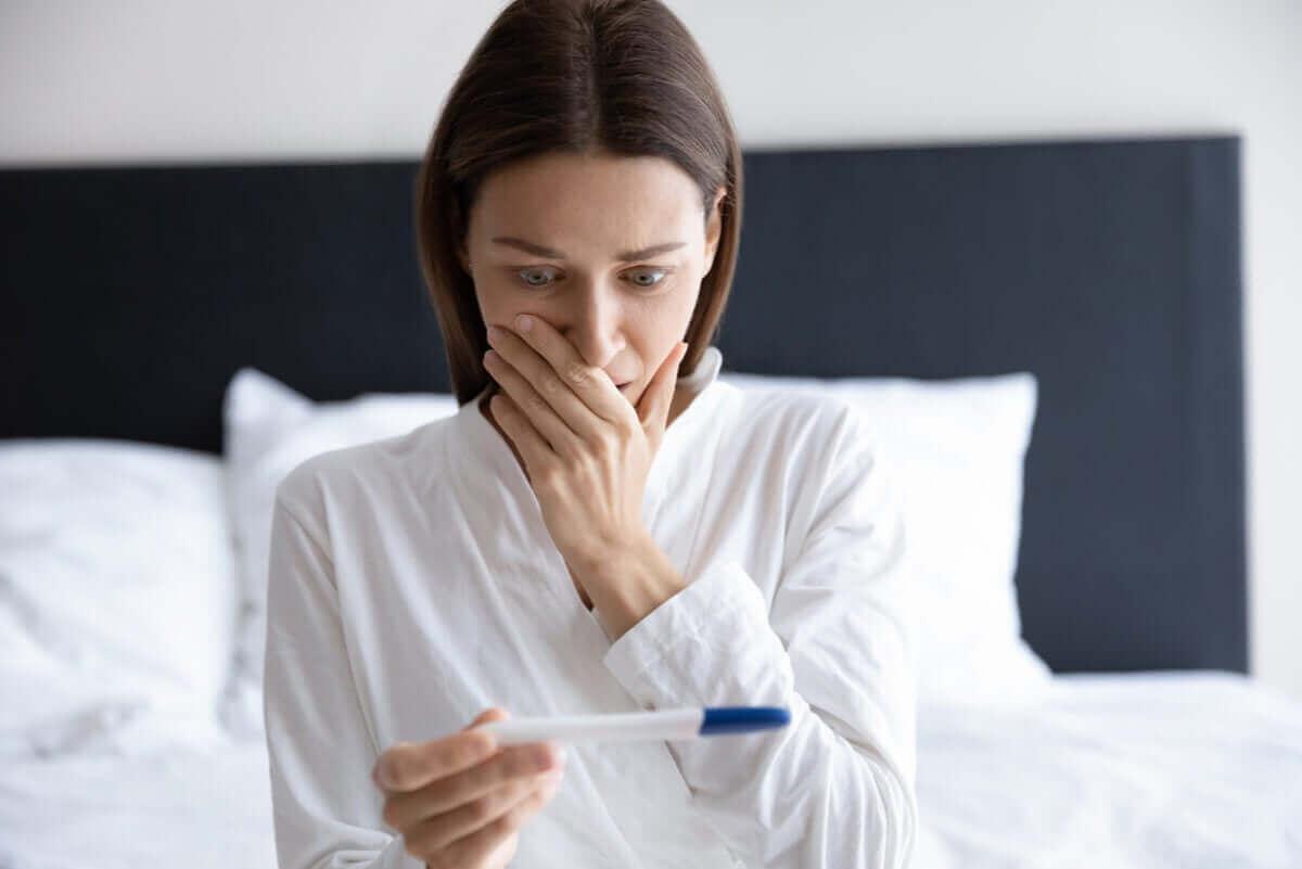 kvinna tittar på graviditetstester hemma