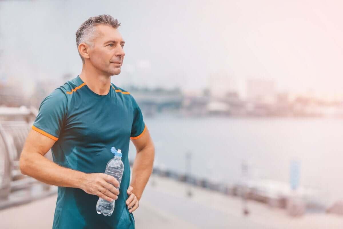man som dricker vatten efter att han motionerat