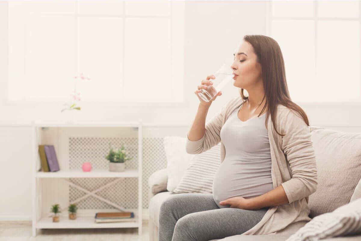 cystit under din graviditet: gravid kvinna dricker vatten