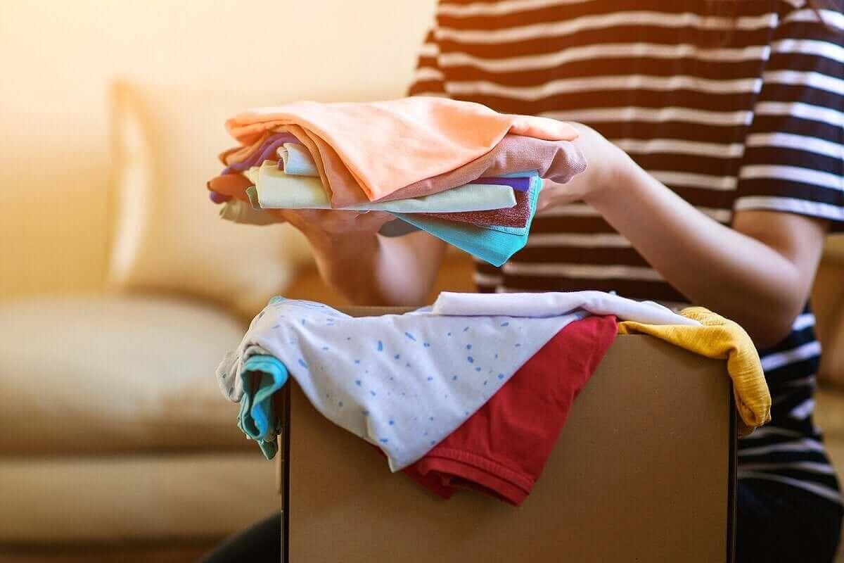 kvinna som förespråkar cirkulärt mode packar kläder för att donera