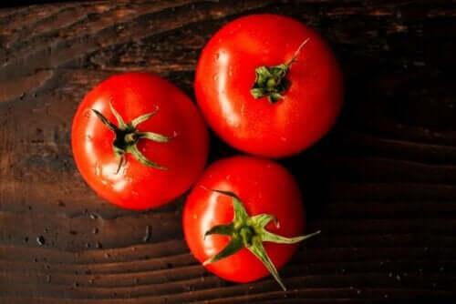 tre röda tomater på ett bord