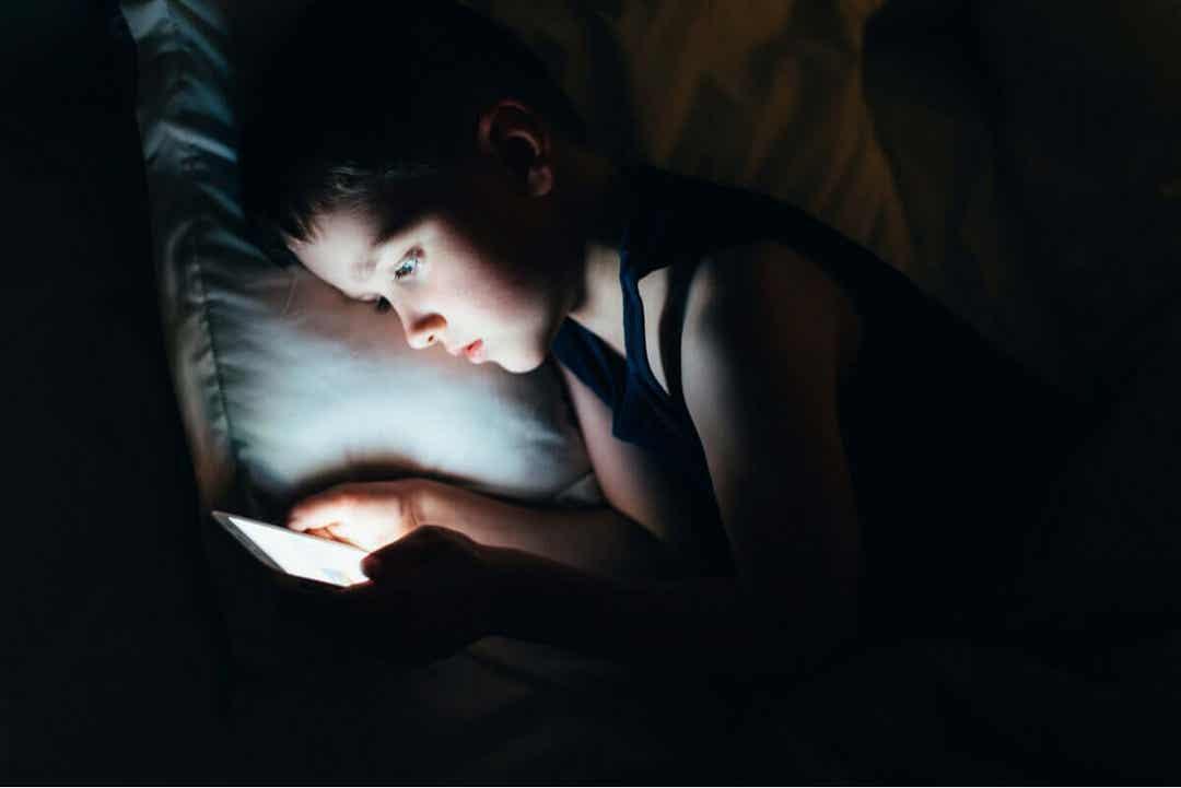 Sociala medier: barn tittar på mobil under täcket