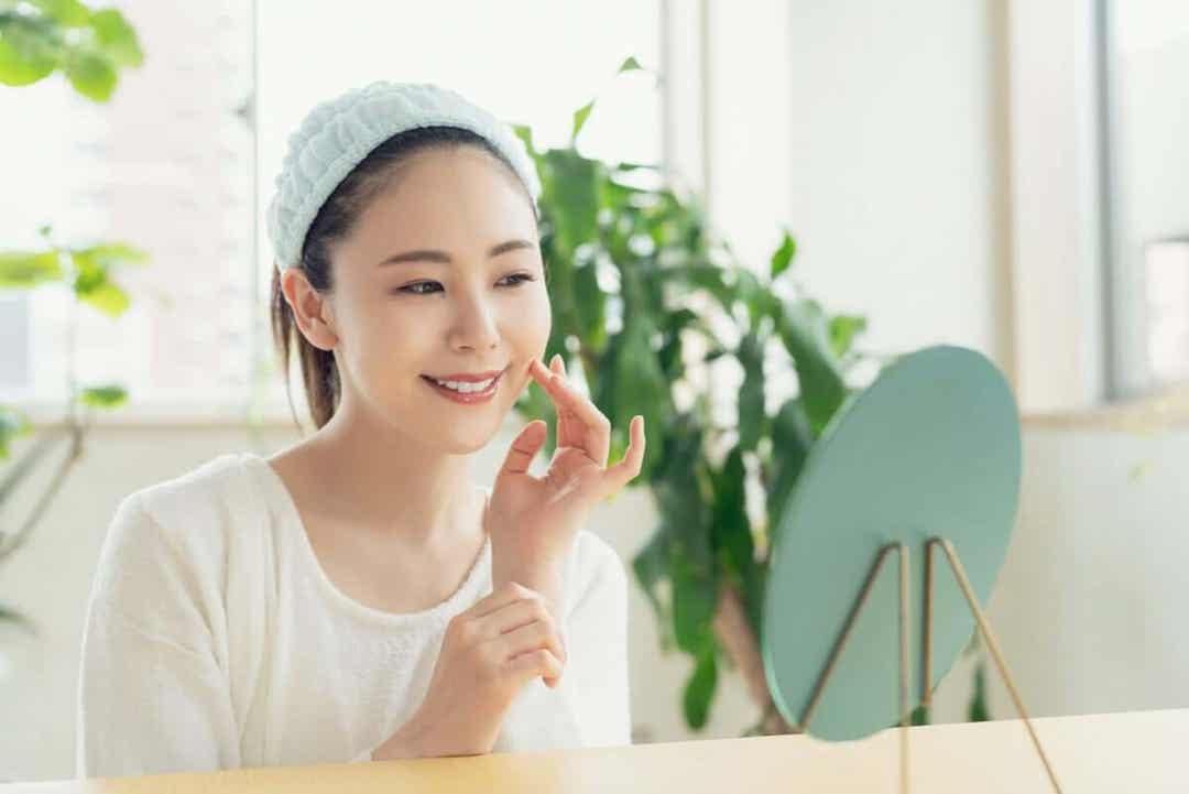 peptider gynnar huden: kvinna smörjer in ansiktet