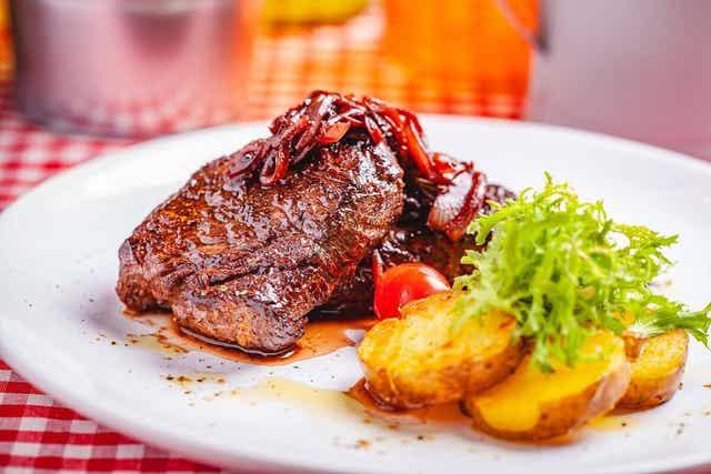 Kött och lök upplagd på en tallrik.