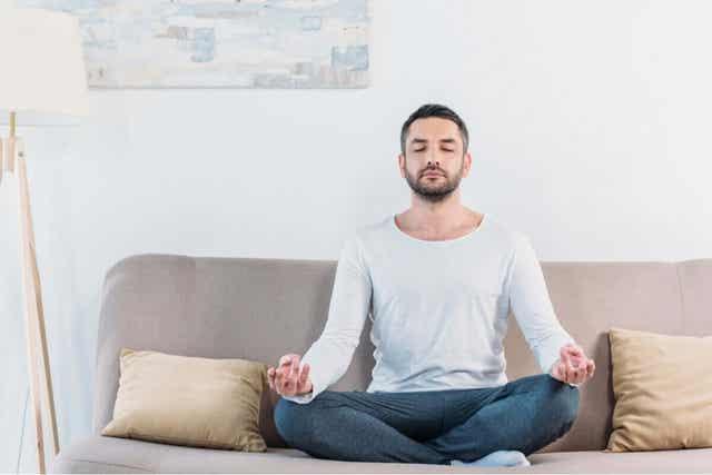 En man sitter på soffan och mediterar.
