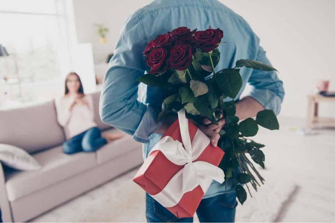 man kommer med rosor och present