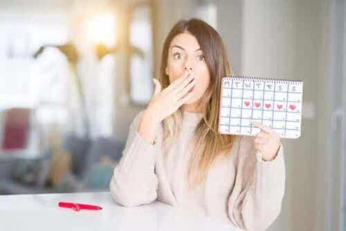 kvinna visar kalender med mensdagar utmärkta