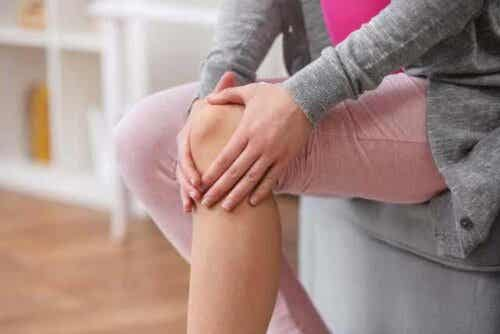 kvinna håller sig för knät