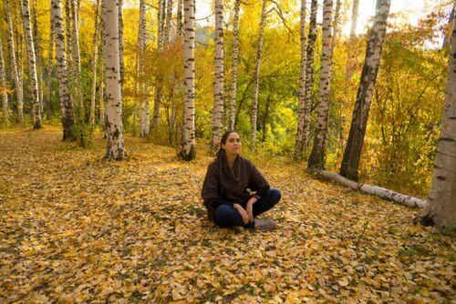 En kvinna som mediterar i skogen