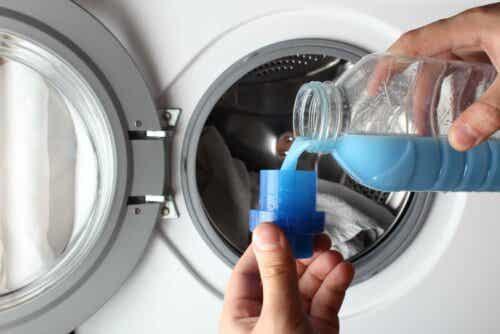 En person som häller tvättmedel i ett lock.