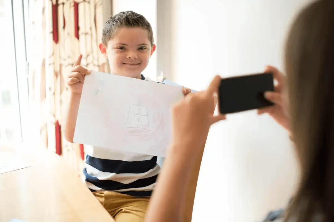 pojke håller upp teckning