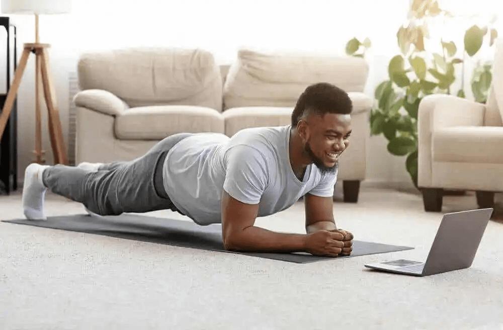 man gör plankan framför laptop